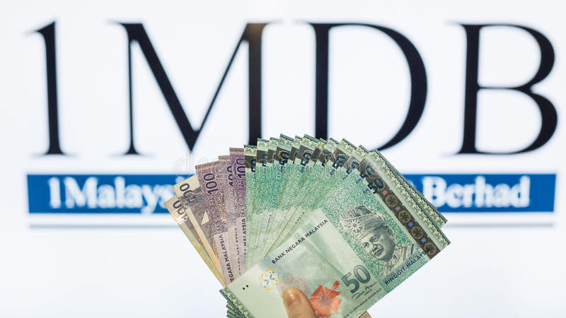 Man holding Malaysia Ringgit with burr 1MDB background indicating the US Government inves royalty free stock images