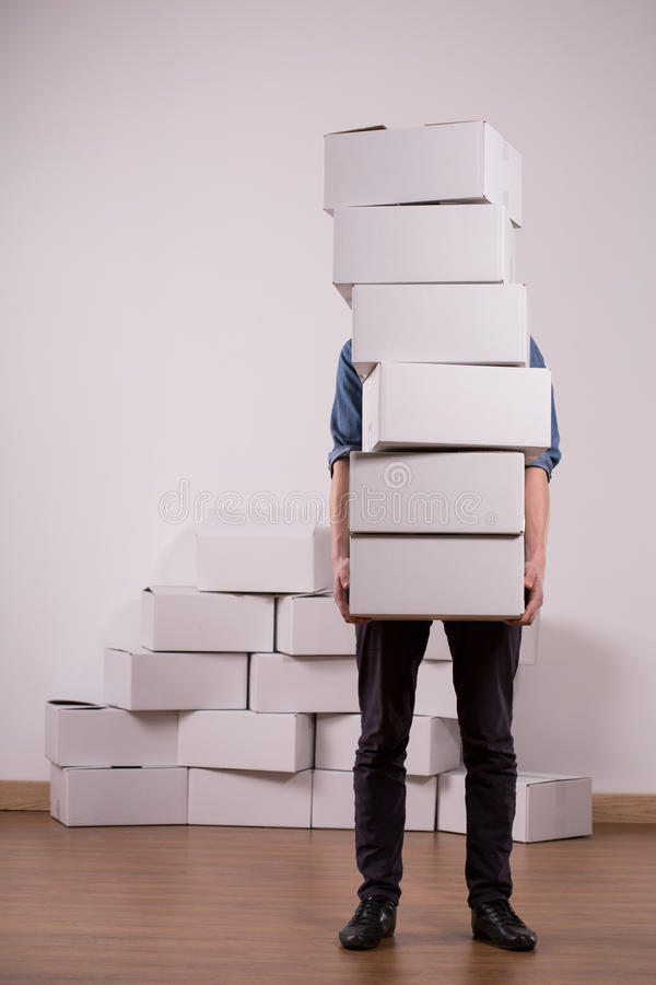 Man holding many cardboard boxes. Image of man holding many cardboard boxes during move stock photo