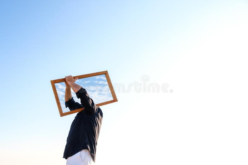 Man holding a mirror over his shoulder so that it covers his head in the outdoors. stock images