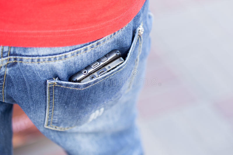 Man holding mobile phones in unsafety way in back pocket, an ea royalty free stock photography