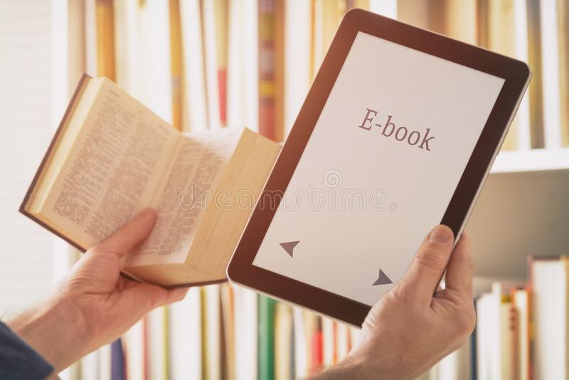 Man holding a modern ebook reader and book stock photo