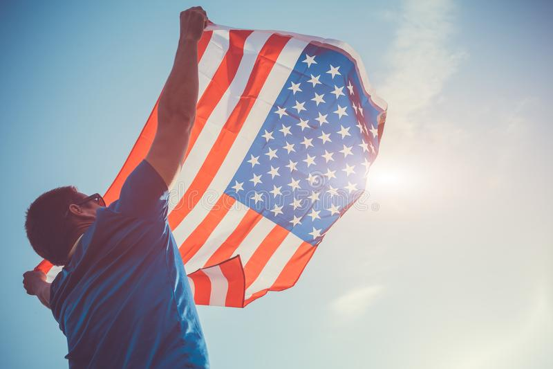 Man holding national USA flag. Celebrating Independence Day of America. July 4th royalty free stock photo