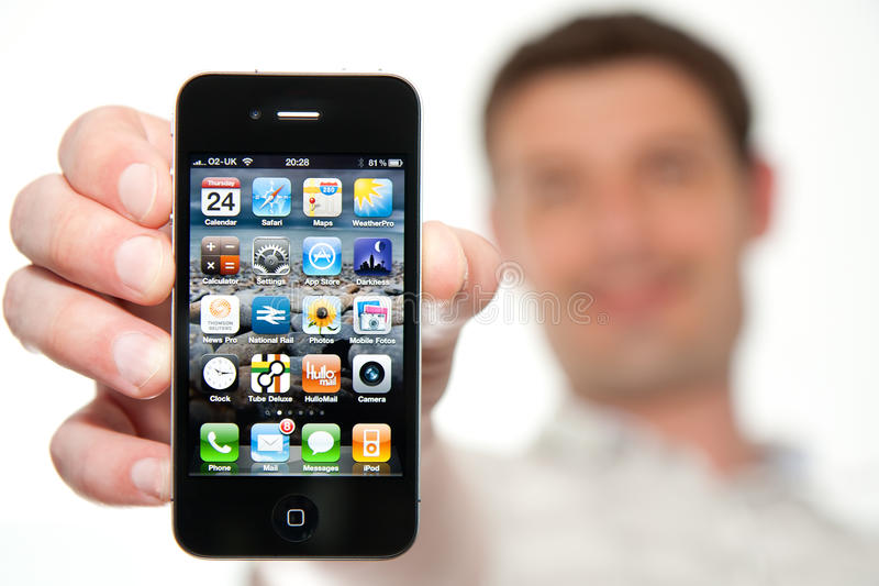 Man Holding a New iPhone 4. A smiling man holds a new iPhone 4 close to the camera. Focus on the phone stock image
