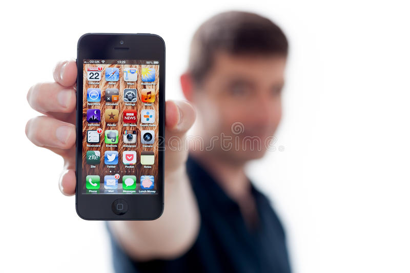 Man Holding a New iPhone 5. A man holds a brand new iPhone 5 towards the camera. Focus on the phone with shallow depth of field stock image