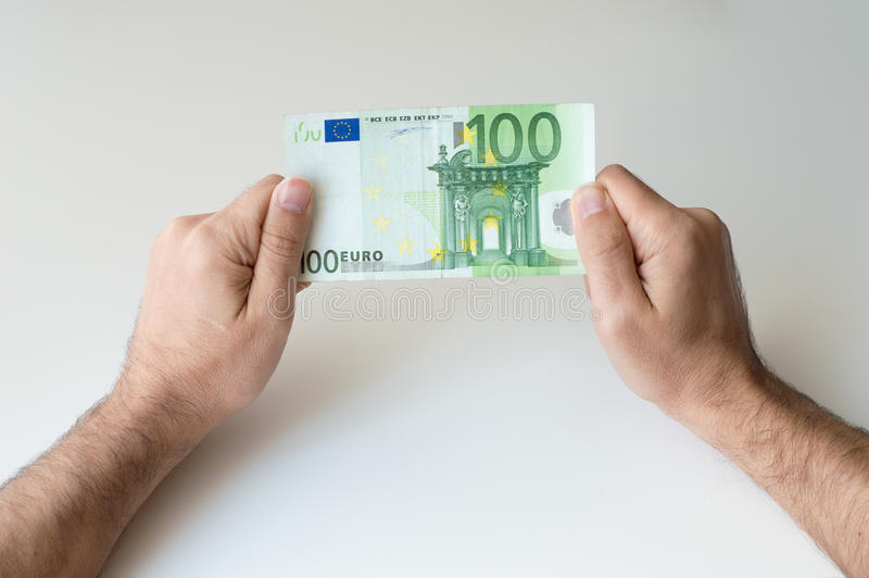 Man holding one hundred Euro banknote. In his hands stock image