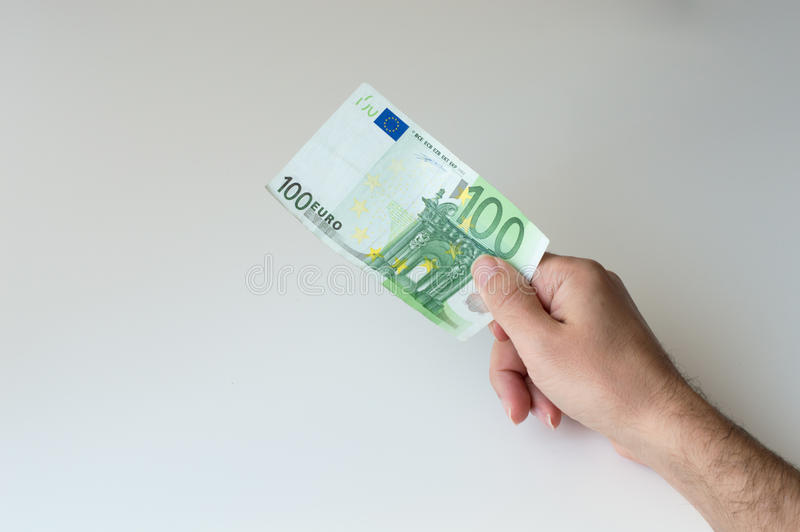 Man holding one hundred Euro banknote. In his hands royalty free stock photography