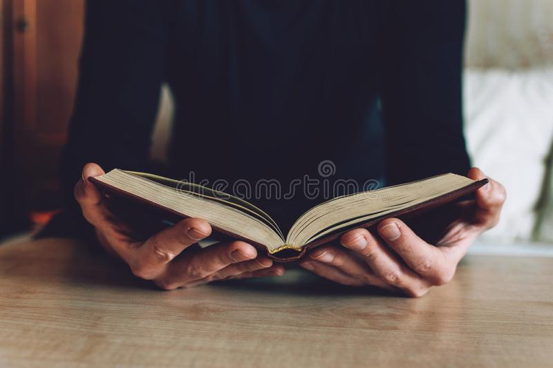 Man holding Open book in hands. Male hands hold a hardcover book. Education, literature, knowledge, reading concept. Copy space stock photo