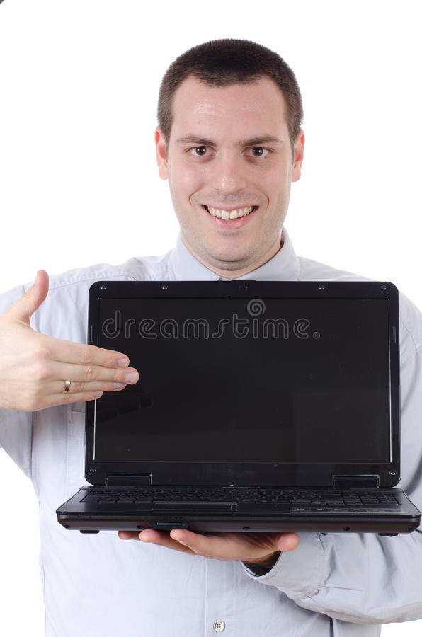 Man holding open laptop showing it with a smile. Young man, holding a laptop computer in front of him, showing pointing his hand at the screen royalty free stock photos