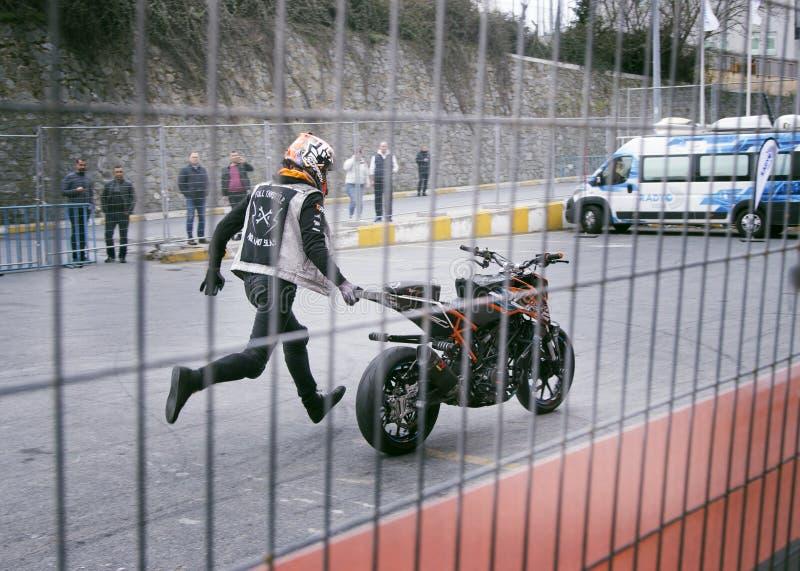 Man Holding Orange and Black Sports Bike on Asphalt Road stock images