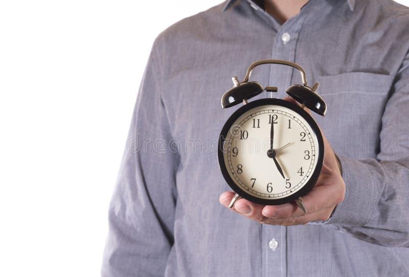 Man holding out a retro alarm clock royalty free stock photos