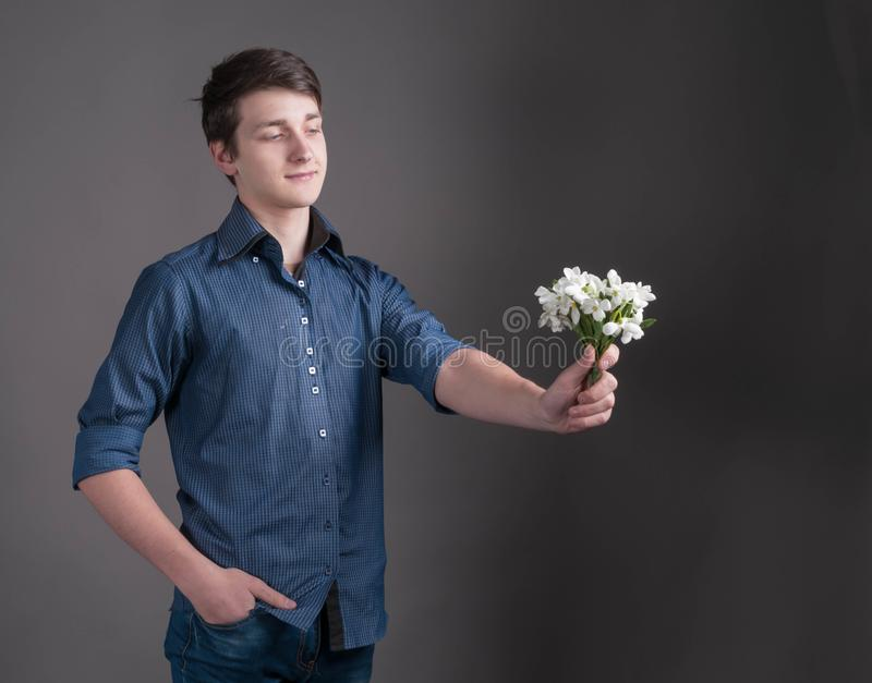 Man holding in outstretched hand bouquet with white snowdrops. Handsome smiling young man in blue shirt holding in outstretched hand bouquet with white snowdrops stock photography