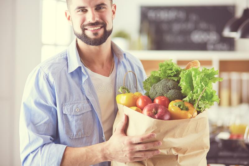 Man holding paper bag full of groceries on the kitchen background. Shopping and healthy food concept.  stock photo