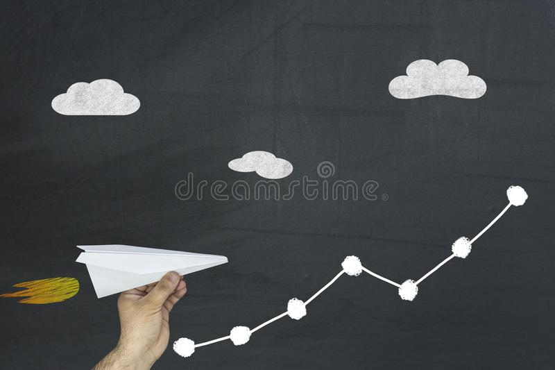 Man holding paper plane flying up on growing graph arrow chart on chalkboard. Business finance concept. stock photos