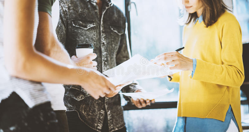 Man holding the papers in his hands and woman signing document. Coworkers team working in sunny office near the window stock photography