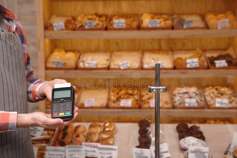 Man holding payment terminal in bakery. Space for text. Man holding payment terminal in bakery, closeup. Space for text royalty free stock photo