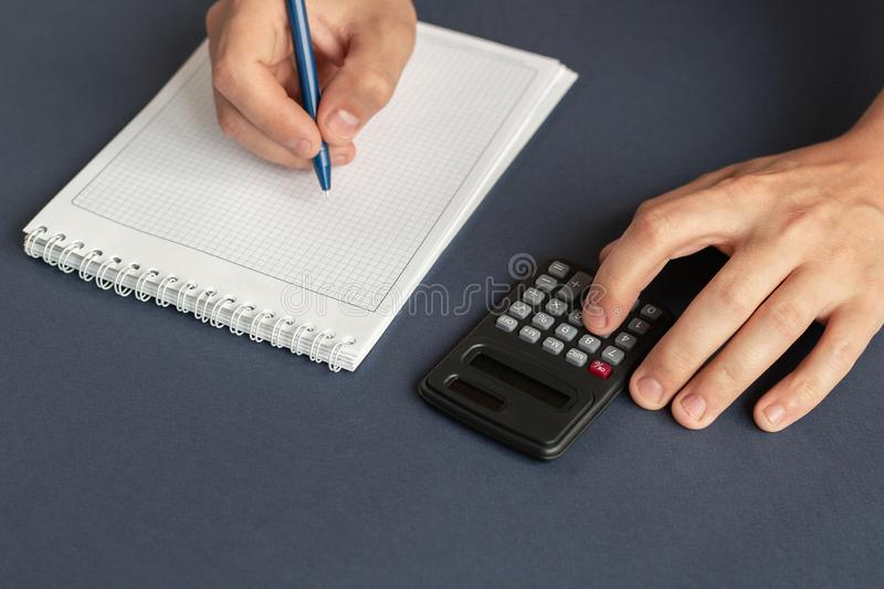 A man holding pen, taking notes and using a calculator royalty free stock photos