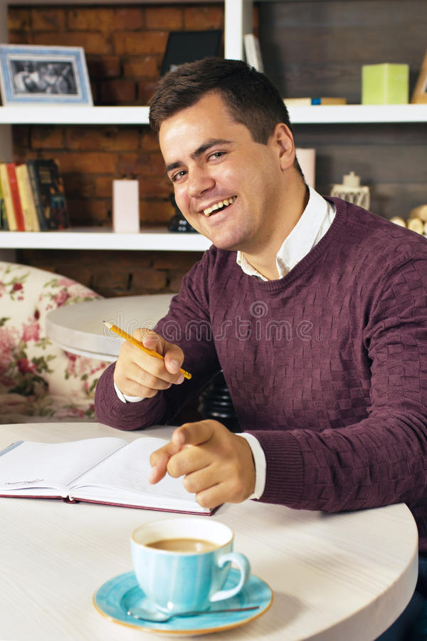 Man holding pencil and writing on a paper in the diary. Young man holding a pencil, writing on a paper in the diary stock image