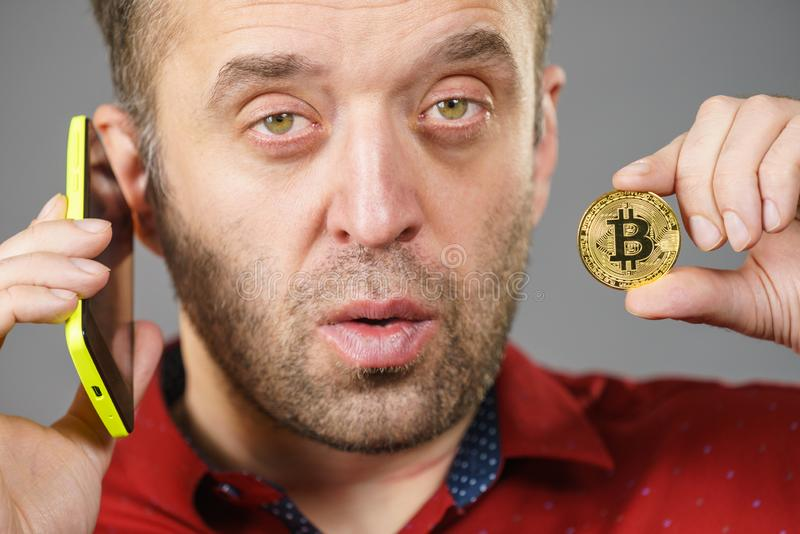 Man with bitcoin talking on phone stock photo