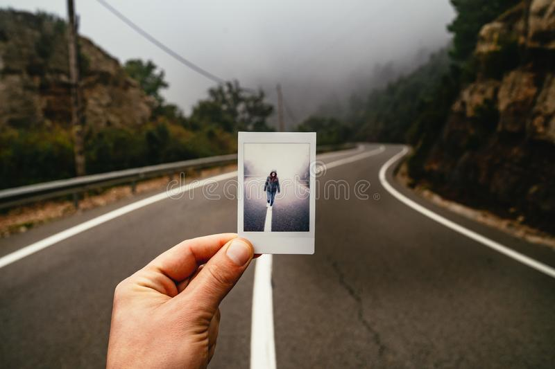 Man holding a photo in a misty road royalty free stock photography
