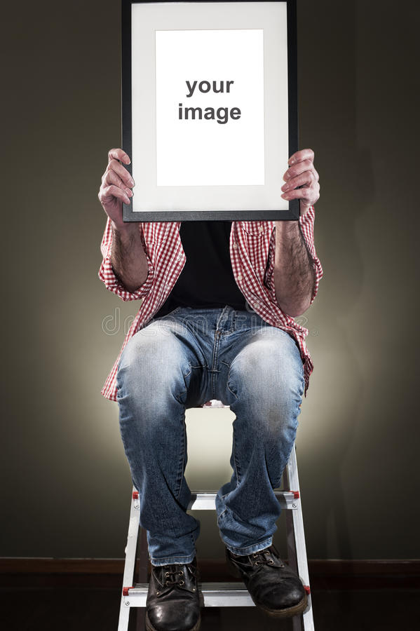 Man holding picture frame. While climbing on ladder stock photo
