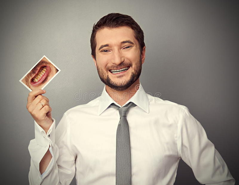 Man holding picture with yellow teeth. Smiley healthy man holding picture with dirty yellow teeth stock photo