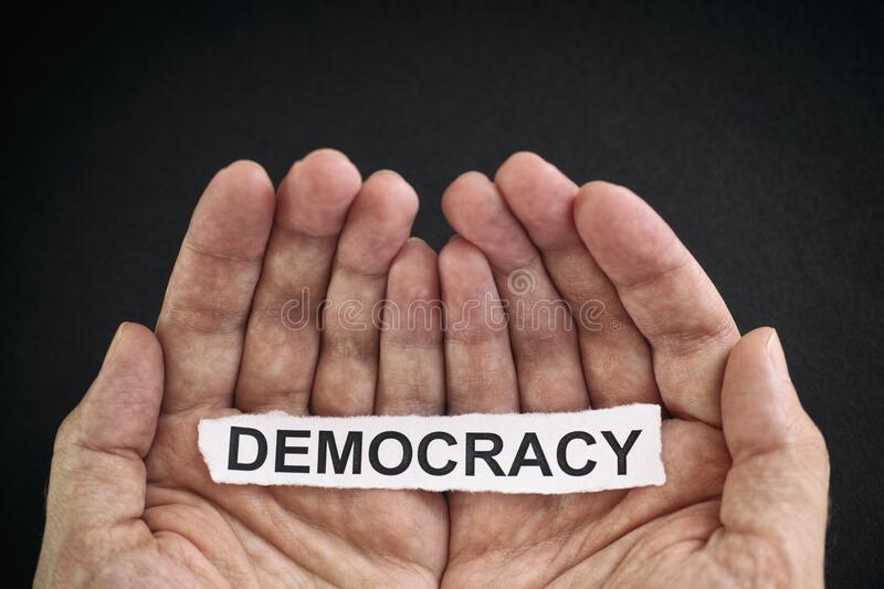 Man holding piece of paper with the word Democracy in his hands stock image
