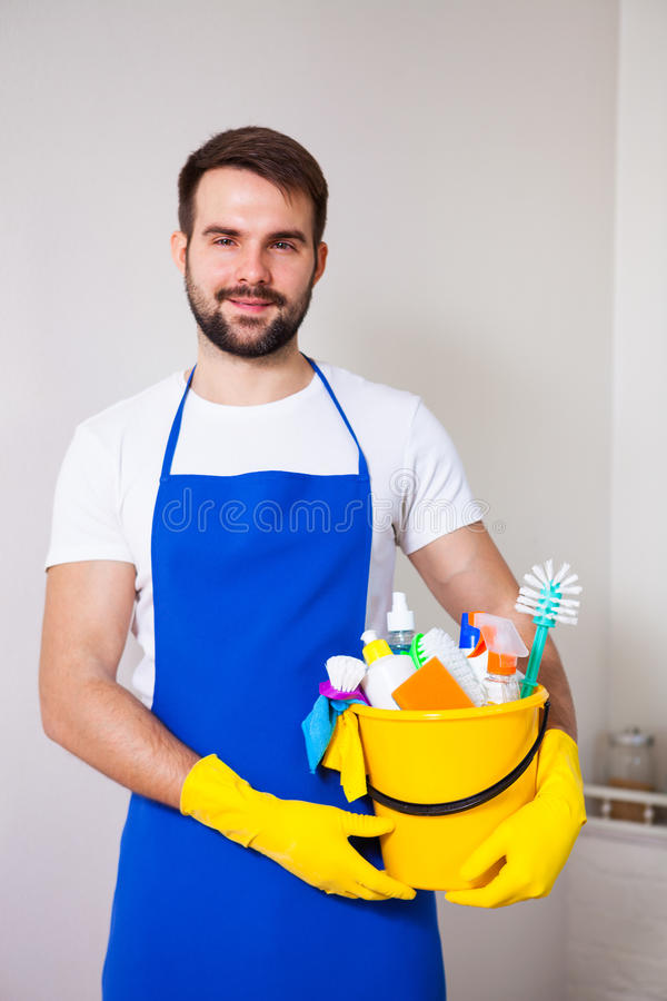 Man holding plastic bucket with bottles and brushes, gloves and stock photography