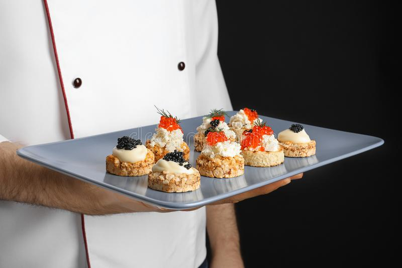 Man holding plate with caviar appetizers stock photography