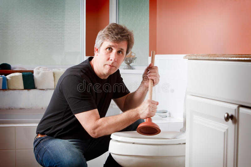 A man holding a plunger to clear a plugged toilet. A man looking at the camera holding a plunger by a toilet stock photos