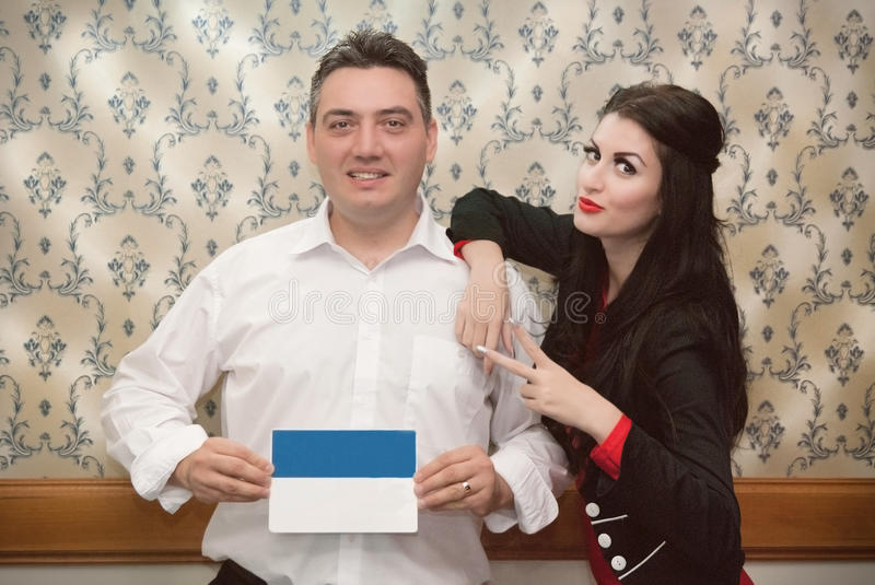 Man holding a poster and a girl leaning on his shoulder stock image