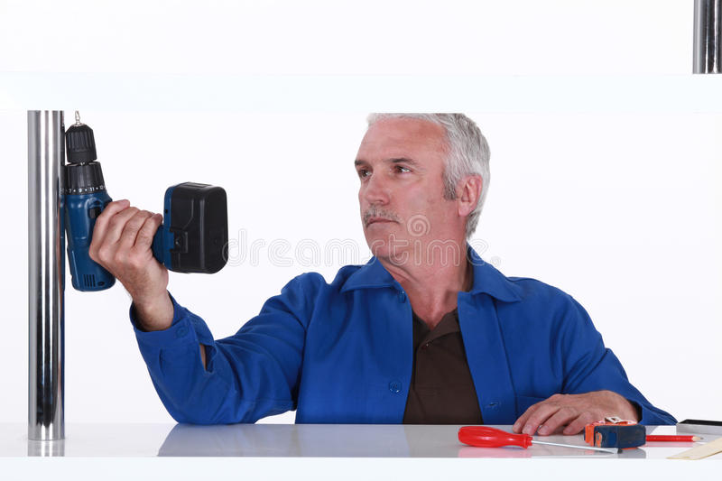Man holding a power tool. In one hand stock photos
