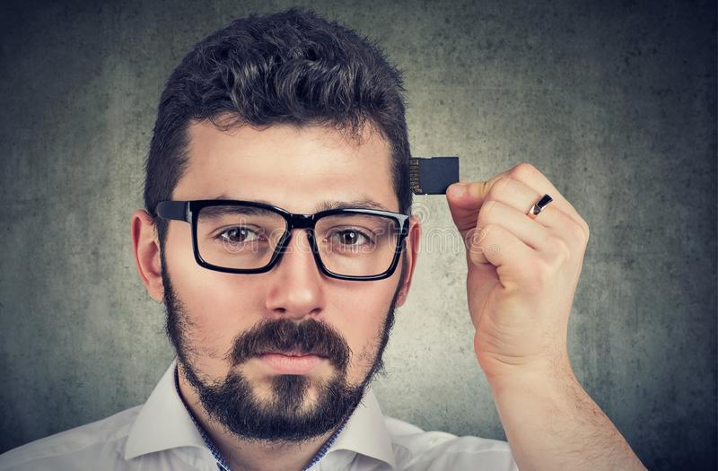Man holding a processor memory card by his head stock photo