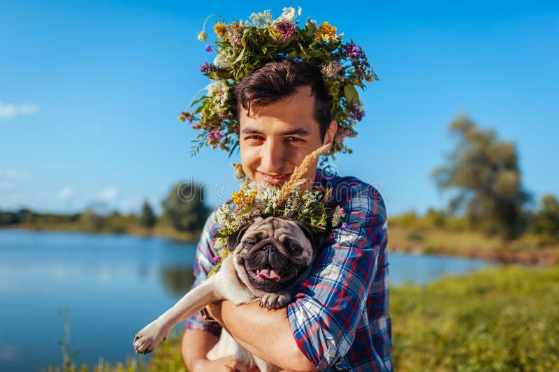 Man holding pug dog with flower wreath on head. Man walking with pet by summer lake. Man holding pug dog with flower wreath on head. Happy man walking with pet stock photography