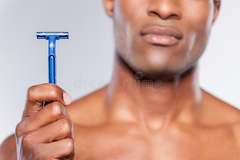 Man holding razor blade. Cropped image of young shirtless African man holding razor blade while standing isolated on grey background royalty free stock photography