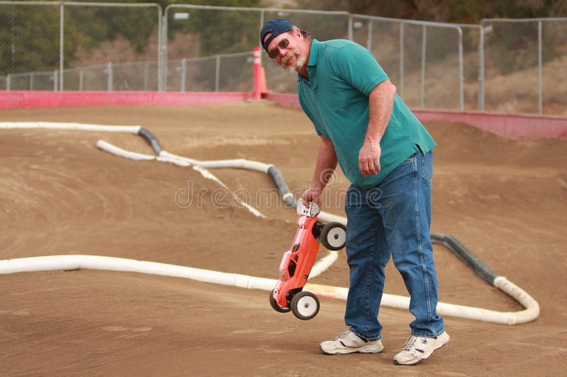Man holding RC car at race track. A man wearing sunglasses and baseball cap is picking up a radio control car (or RC car) at a race track. He is the pit crew royalty free stock photography
