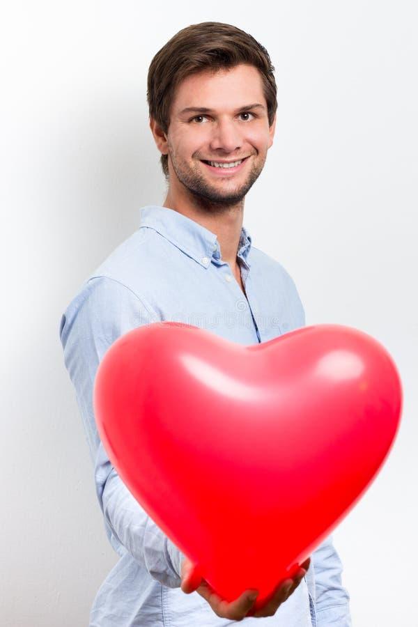 Man holding a red heart balloon stock photos