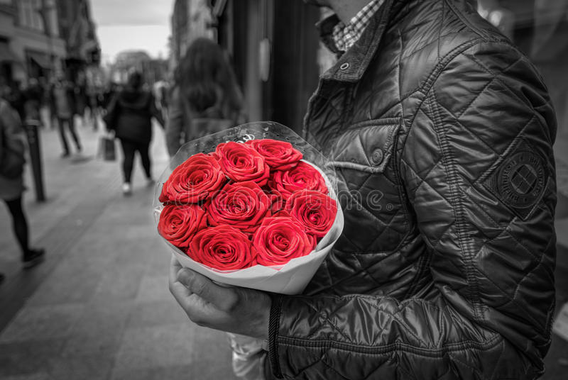 Man holding red rose bouquet