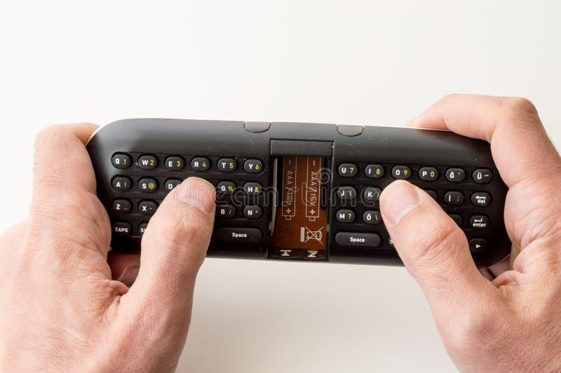 Man holding a remote control keypad. Man's hands holding a remote control keypad royalty free stock photos