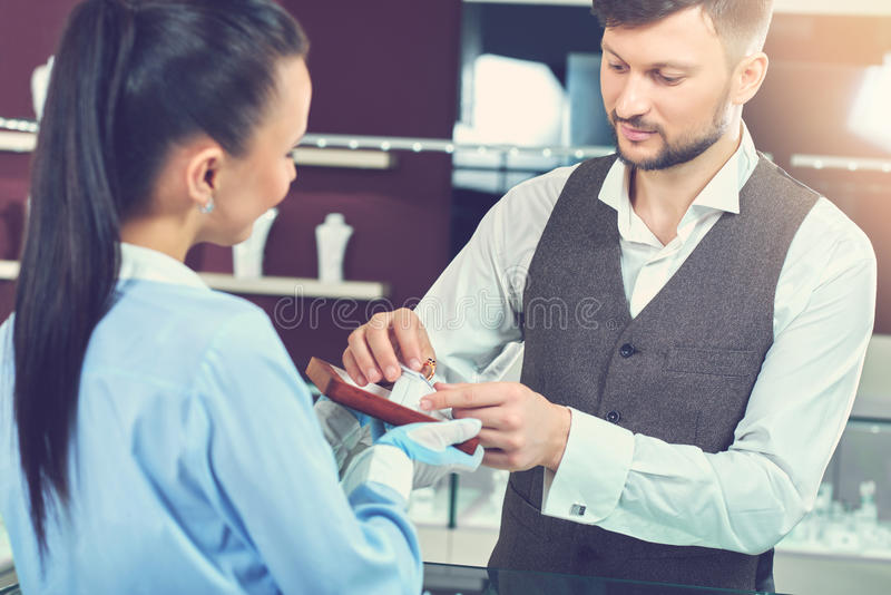 Man holding ring and choosing present at jewelry store. stock photography