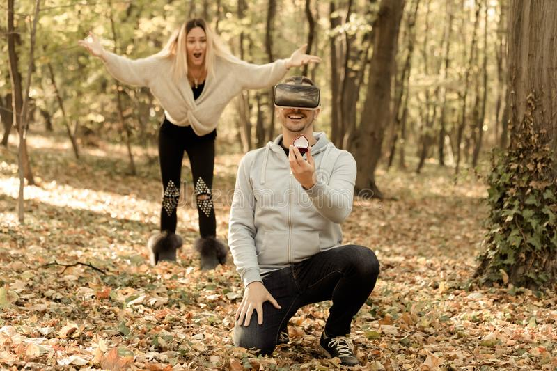 Man holding ring and proposing virtual girlfriend . His real girlfriend is shocked. Virtual proposal. His real girlfriend is shocked royalty free stock photo