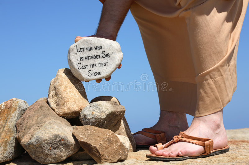 Man holding rock with bible verse John 8:7. A man holds a white rock inscribed with a bible verse from John 8:7 - Let him who is without sin cast the first stone royalty free stock image
