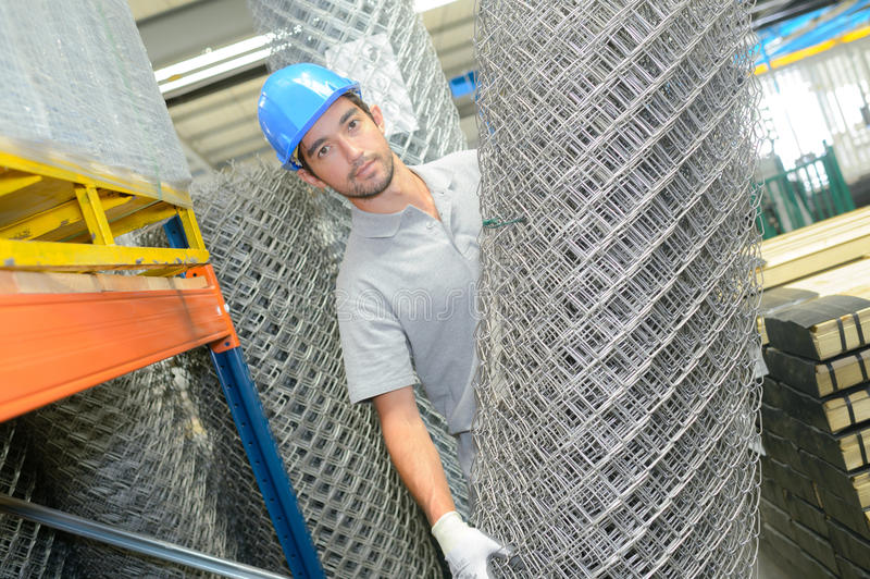 Man holding roll metal fencing wire stock photography