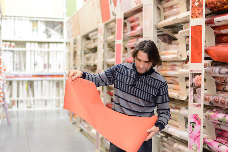 Man holding a roll of wallpaper in the store. Man holding a roll of a wallpaper in the store royalty free stock image