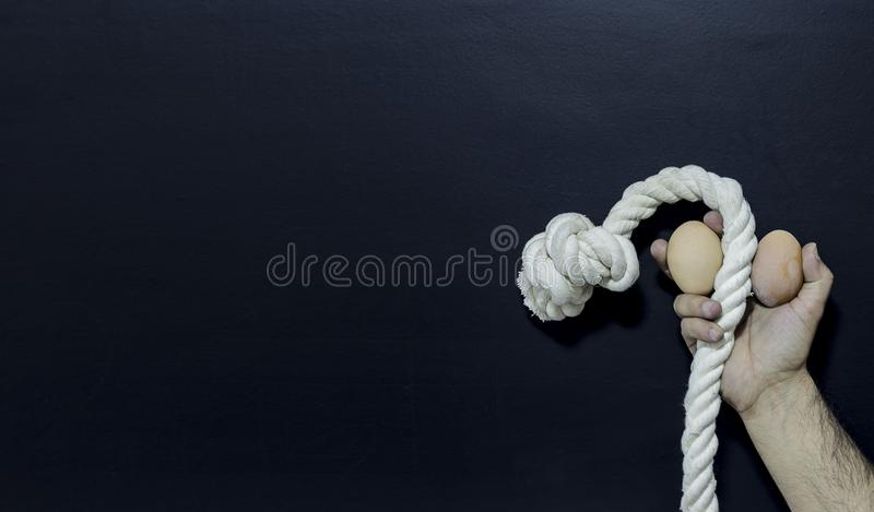 Man holding rope and two eggs showing erectile dysfunction stock image