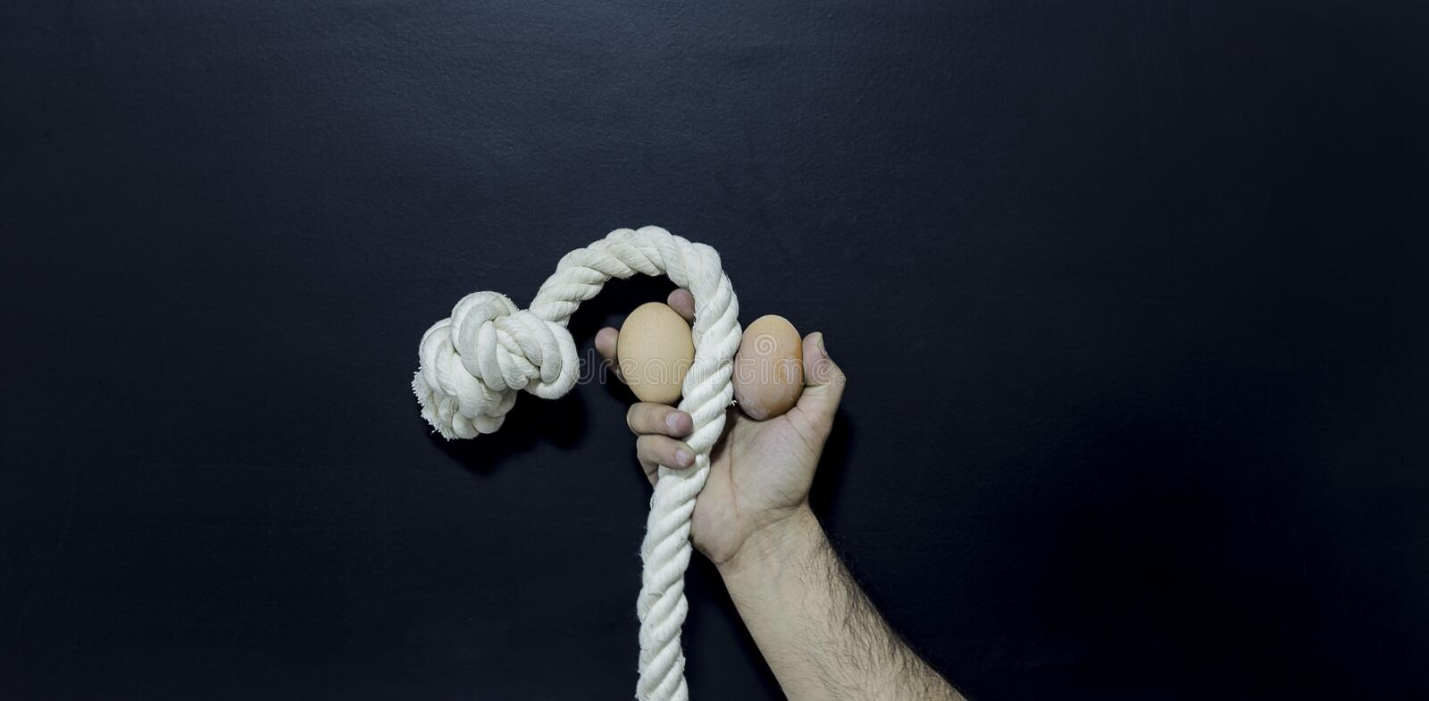 Man holding rope and two eggs showing erectile dysfunction stock photography