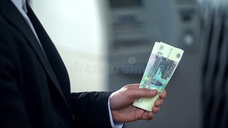 Man holding Russian rubles banknotes withdrawn from ATM, good service, tourism royalty free stock image