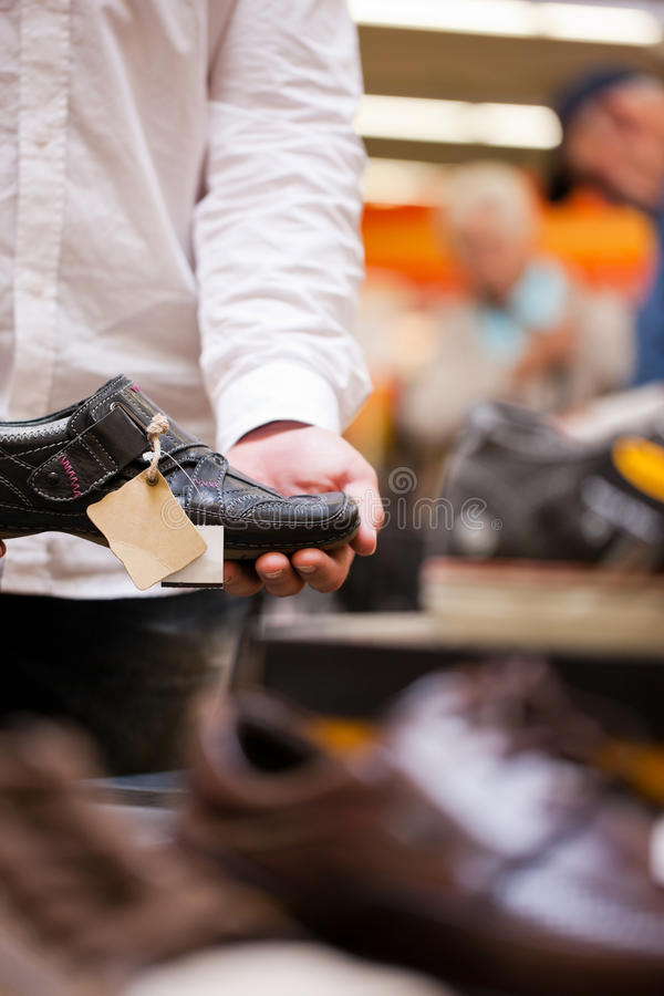 Man Holding Shoe with Price Tag Hanging royalty free stock photo