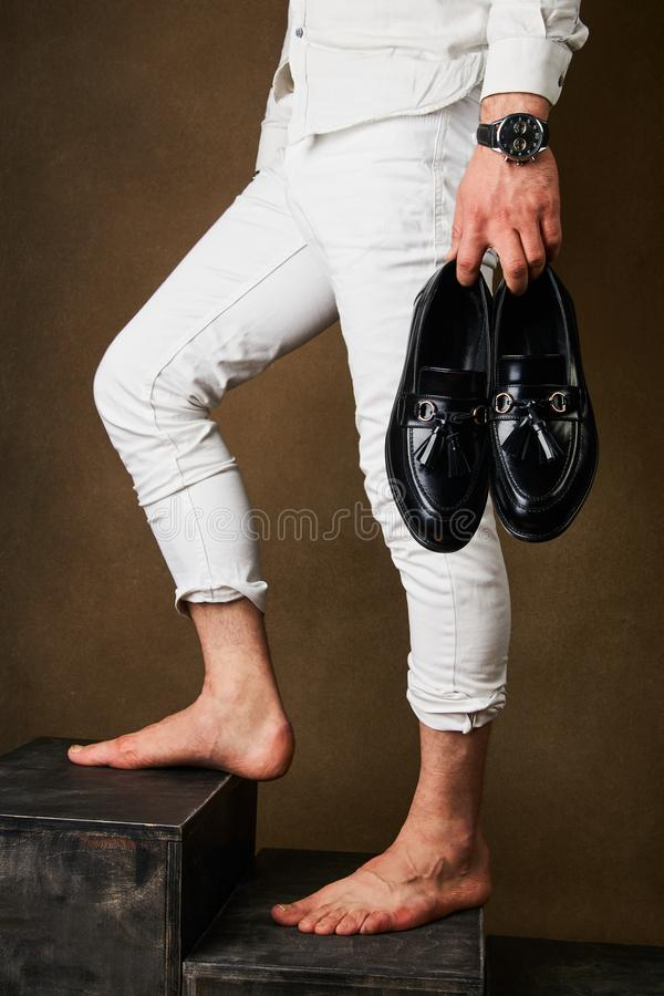 Mens fashion concept with mens hold black leather shoes in hand stock photography