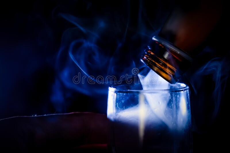 The man holding shot of dring in his hand and flow of steam or evil spirit flow out of and fill in the glass royalty free stock photo