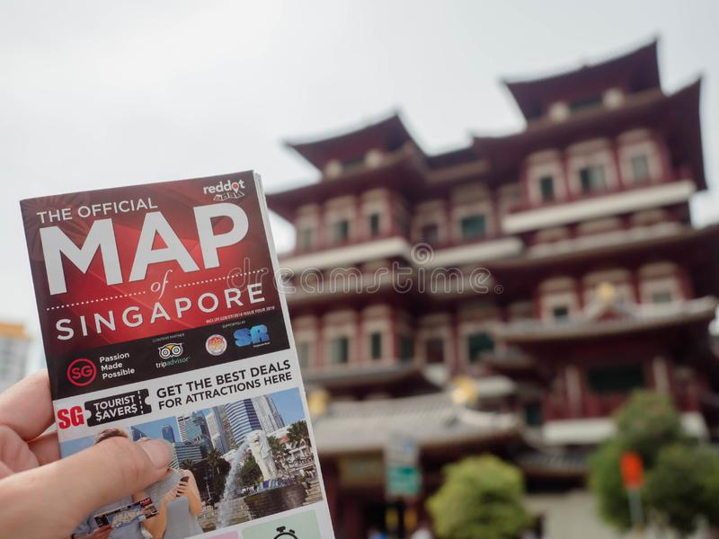 Man holding a Singapore map The back is Buddha Toothe Relic Temple in Chinatown Singapore stock image
